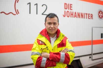 """Guo Wei C., 24 Jahre, Notfallsanitäter bei den Johannitern. """"Die Belastung trifft nicht nur uns, sondern jeden. Mit dem Einsatz von allen bewältigen wir die Krise."""""""